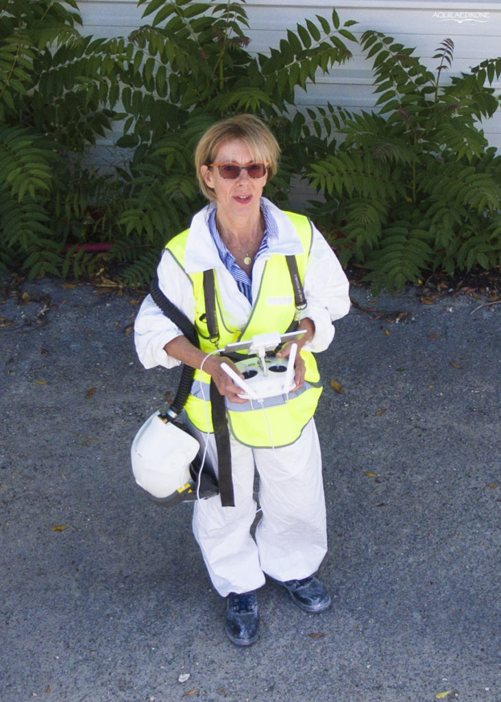 Photo de Anne Petit en train de piloter un drone sur un chantier